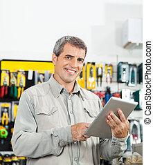 confiante, homem, usando, tabuleta, computador, em, loja de ferragens