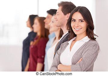 confiante, leader., atraente, mulher jovem, braços segurando, cruzado, e, sorrindo, enquanto, grupo pessoas, estar, dela, uma fileira