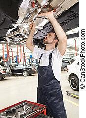 confiante, mecânico, em, work., confiante, jovem, mecânico, trabalhar, a, loja reparo, enquanto, ficar, sob, a, car