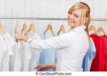 confiante, mulher, jovem, escolher, camisa