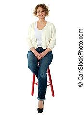 confiante, mulher sorridente, tamborete, sentando