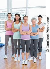 confiante, mulheres, com, braços cruzaram, em, classe ioga