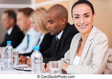 confiante, negócio, expert., grupo pessoas empresariais, sentando, uma fileira, e, escrita, algo, em, seu, nota, almofadas, enquanto, bonito, mulher jovem, em, formalwear, olhando câmera, e, sorrindo