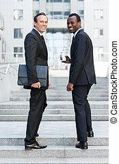 confiante, negócio, pessoas., duração cheia, de, dois, alegre, homens negócio, olhar ombro, e, sorrindo, enquanto, ficar, ligado, escadaria