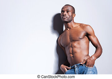 Confidence and masculinity. Handsome young shirtless African man looking away and holding hands in pockets while leaning at the grey wall