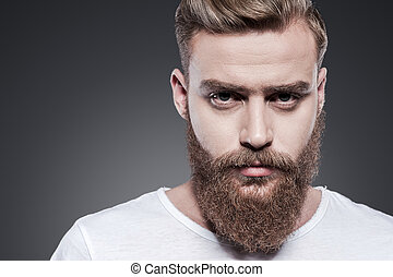 Confidence and masculinity. Portrait of handsome young bearded man looking at camera while standing against grey background