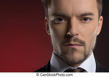 Confidence businessman. Portrait of confident young businessman looking at camera while isolated on red