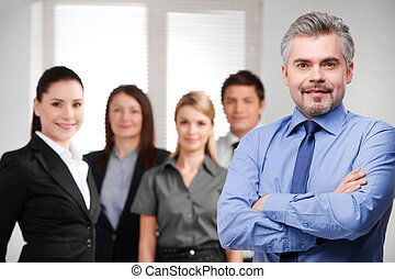 Confident adult businessman looking successful with crossed arms. Blur smiling business team on background