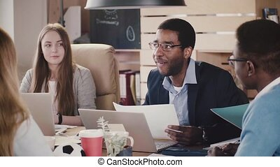 Confident African American CEO businessman leading an argument at mixed ethnicity meeting in modern office slow motion.