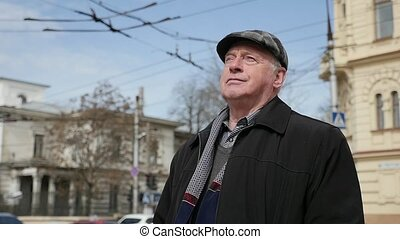 Confident aged man standing and thinking in a busy street in...
