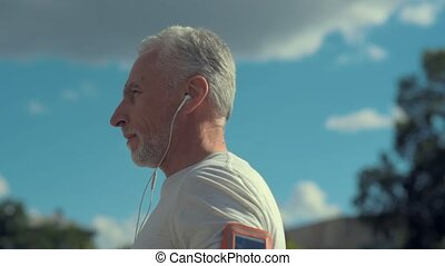 Regular exercises. Portrait of a confident senior man listening to music and holding hands on the waistline while going to train