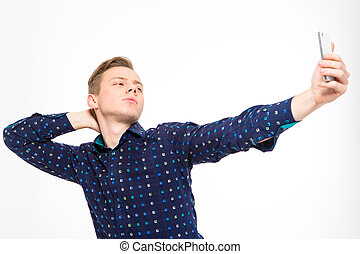 Confident amusing young male making selfie using cellphone
