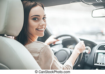 Confident and beautiful. Rear view of attractive young woman in casual wear looking over her shoulder while driving a car