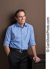 Confident and cheerful executive . Cheerful mature businessman standing with his hand in the pocket and looking away
