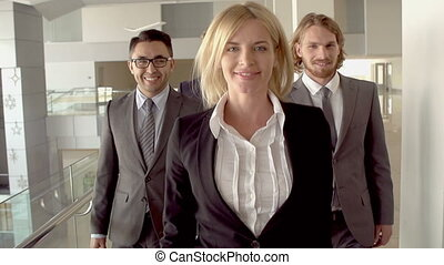 Slow-motion of smiley blond woman walking towards camera, her male colleagues following her