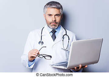 Confident and experienced doctor. Confident mature doctor working holding laptop and looking at camera while standing against grey background