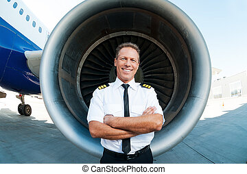 Confident and experienced pilot. Confident male pilot in uniform keeping arms crossed and smiling while standing in front of airplane turbine engine