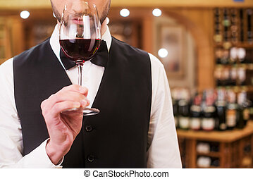 Confident and experienced sommelier. Close-up of confident young man in waistcoat and bow tie holding wine glass with red wine and smelling it