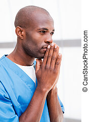Confident and experienced surgeon. Side view of thoughtful young African doctor in blue uniform holding hands clasped near face and looking away and keeping arms crossed
