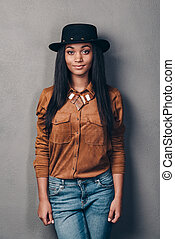 Confident and gorgeous. Beautiful young African woman in hat looking at camera while standing against grey background
