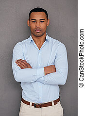 Confident and handsome. Confident young African man keeping arms crossed and looking at camera while standing against grey background