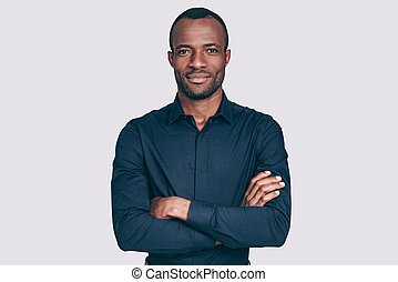 Confident and handsome. Handsome young African man keeping arms crossed and looking at camera while standing against grey background