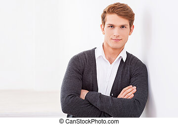 Confident and handsome. Handsome young man keeping arms crossed and looking at camera while leaning at the wall