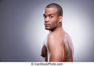 Confident and handsome. Young shirtless African man looking over shoulder while standing against grey background