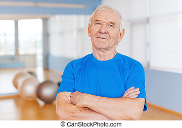 Confident and healthy. Confident senior man keeping arms...