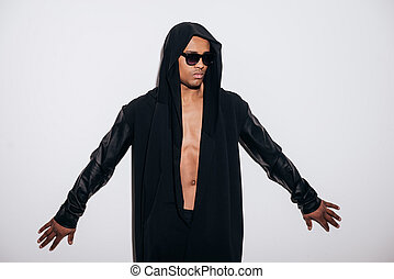 Confident and stylish. Fashionable young African man in hooded shirt standing against white background