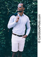 Confident and stylish. Handsome young African man in sunglasses carrying his smart casual jacket on shoulder and looking away while standing against green plant background outdoors