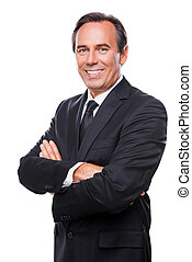 Confident and successful businessman. Waist up of confident mature man in formalwear looking at camera and smiling while keeping arms crossed and standing against white background