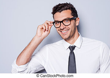 Confident and successful. Portrait of handsome young man in shirt and tie adjusting his eyeglasses and looking at camera while standing against grey background