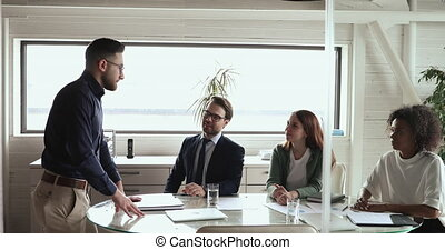 Confident arab businessman company leader manager presenting strategy plan at board corporate meeting room. Middle eastern male boss explaining corporate project training team at group briefing table.