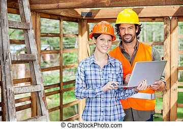 Confident Architects With Laptop At Construction Site
