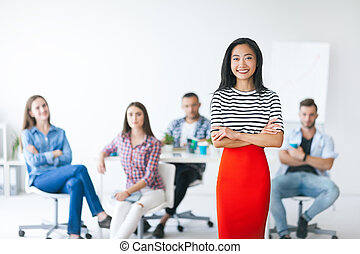 Confident asian business leader with her team on background