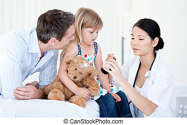 Confident asian female doctor giving syrup to a little girl
