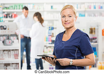 Confident Assistant Holding Digital Tablet At Pharmacy