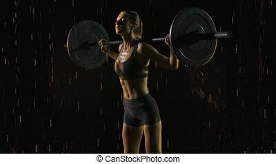 Confident athletic young woman doing overhead squat with barbell. Healthy lifestyle determination. Crossfit. Shot in a dark studio in the rain and staged light. Black background. Slow motion. Close up.