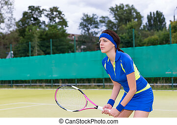 Confident attractive woman in sports clothes playing tennis