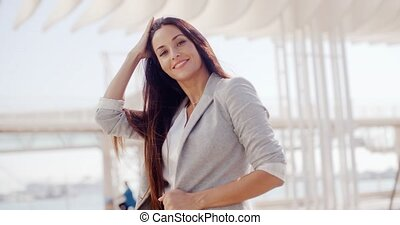 Confident attractive woman with long brown hair standing in...