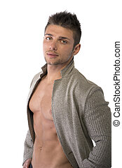 Confident, attractive young man with open jacket on muscular torso, ripped abs and pecs, hands on hips