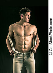 Confident, attractive young man with open vest on muscular ...