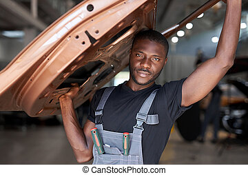 confident auto mechanic holding seperate part of the car