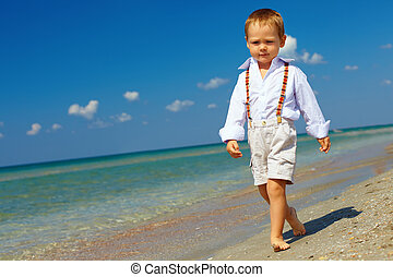confident baby boy goes forward in firm gait, sea beach