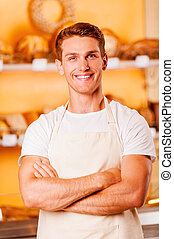 Confident baker. Handsome young man in apron keeping arms...
