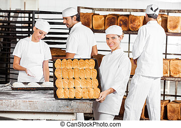 Confident Baker Showing Baked Breads In Bakery