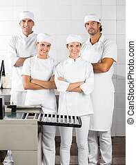Confident Baker's Standing Arms Crossed In Bakery