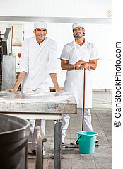 Confident Baker's Standing With Cleaning Equipment -...