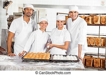 Confident Baker's With Breads Standing At Table